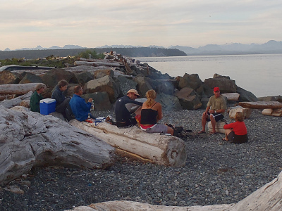 Sitting around a beach fire after a paddle at Ken Forde Park in Campbell River